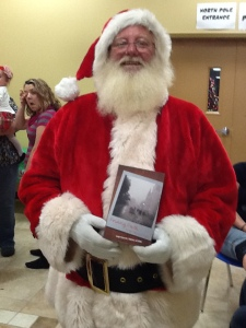 Santa holding his copy of Finding Faith in the City Care Forgot