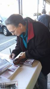 Teena Myers signing book for priest.